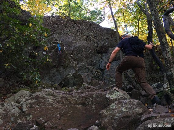 Hiker scrambling over a rocky trail