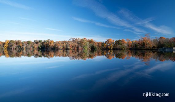 Bright blue Parvin Lake with a line of autumn trees