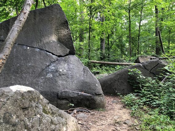 Large angled boulders along a trail