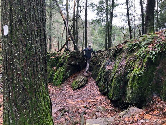 Hiker climbing up a rock crevice