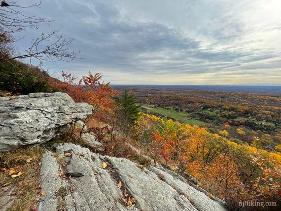 Rock jutting out on a ridge overlooking farms and bright foliage