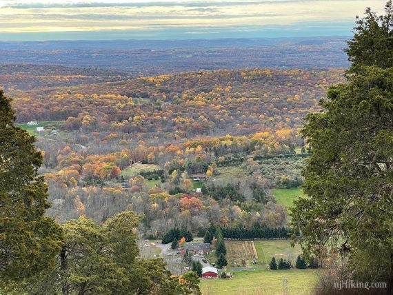 Zoom into a red farmhouse and fall foliage in the valley below