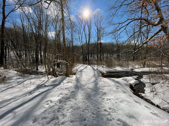 Packed snowy trail and bridge over stream