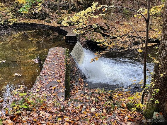 Stone wall and dam with water flowing over it