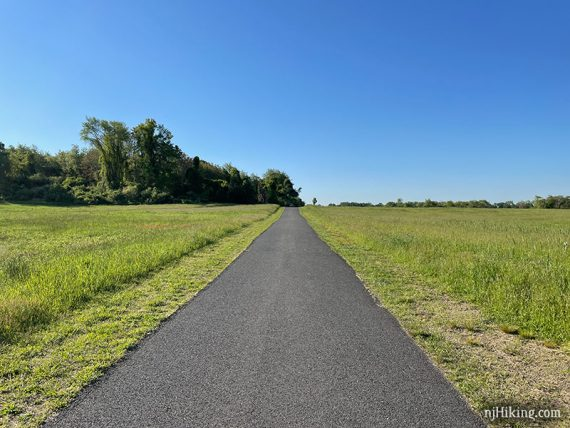 Paved trail with fields on either side