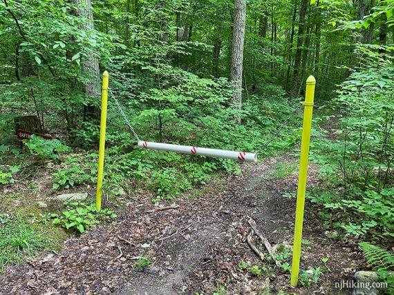 Yellow posts with a chain blocking trail access