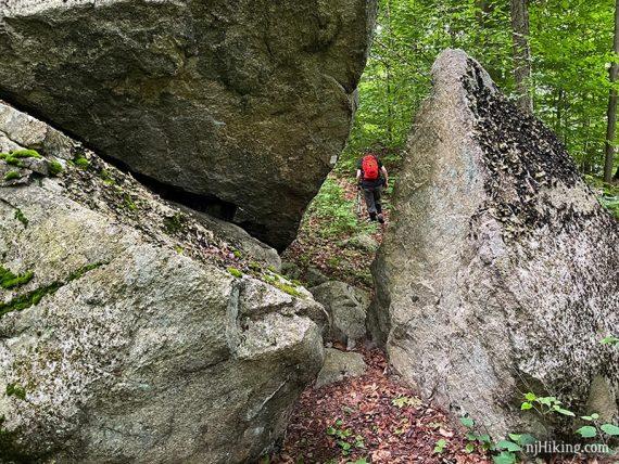 Hiker past a large split rock