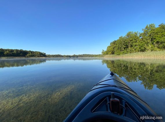 Kayak with vegetation visible in the clear water