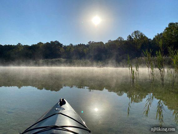 Kayaks in fog on a lake