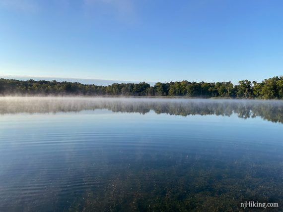 Low layer of fog across a bright blue clear lake