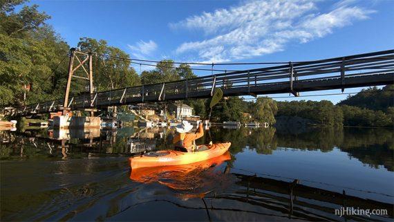 Kayaker paddling under a footbridge