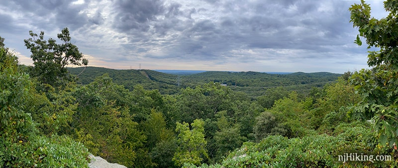 Wide view from an overlook of green hills and power lines in the distance
