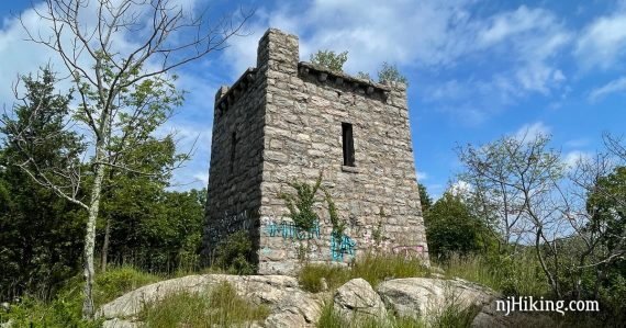 Ruins of a stone water tower on a rocky area in a forest