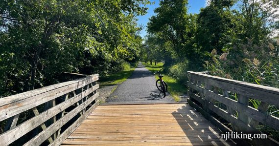 Bike on a paved rail trail after a wooden bridge