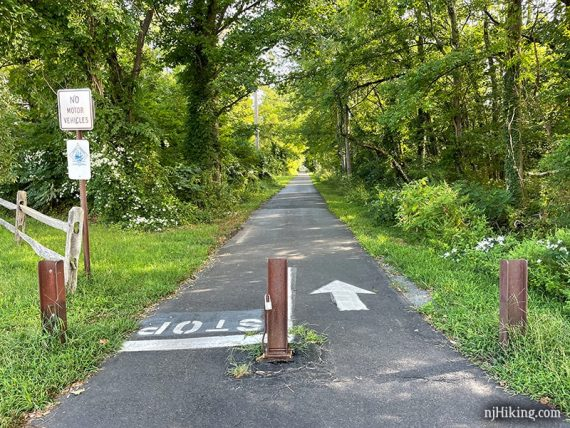 Paved rail trail with metal barrier posts at a crossing