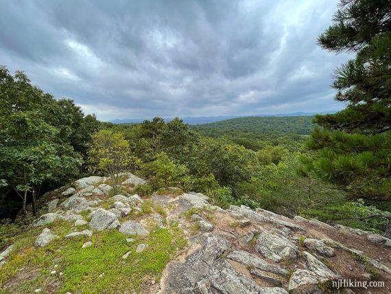 View of green mountains beyond a rocky outcrop