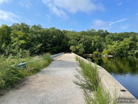 Long flat concrete dam at the end of a lake