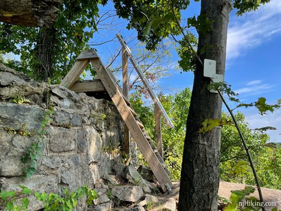 Wooden stile placed as a ladder over a stone wall